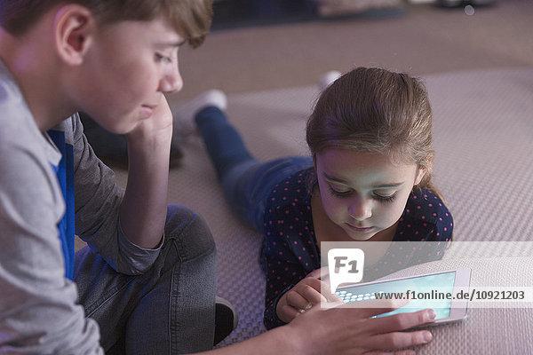 Geschwister spielen Spiel auf digitalem Tablett