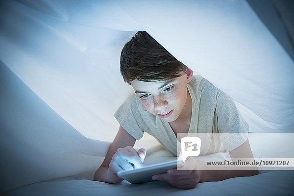 Junge mit digitalem Tablett unter Blatt