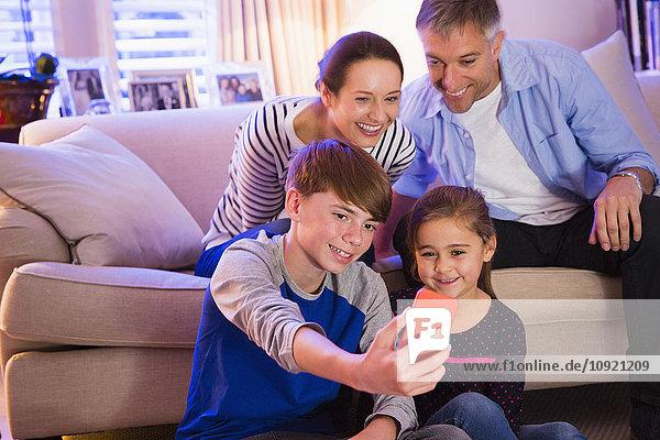Familie nimmt Selfie mit Fotohandy im Wohnzimmer mit.