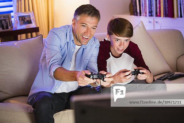 Vater und Sohn spielen Videospiel im Wohnzimmer