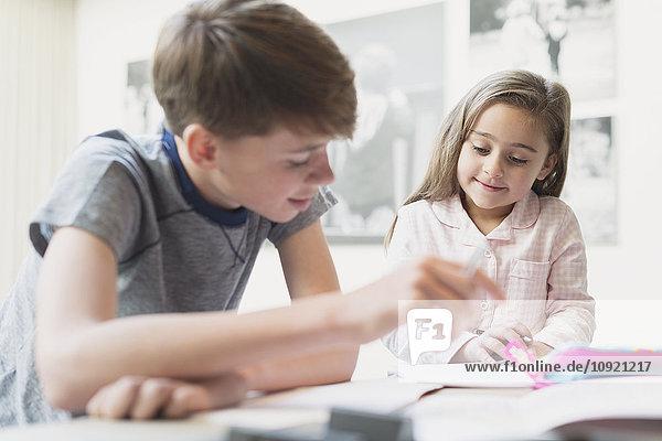 Bruder hilft Schwester bei den Hausaufgaben