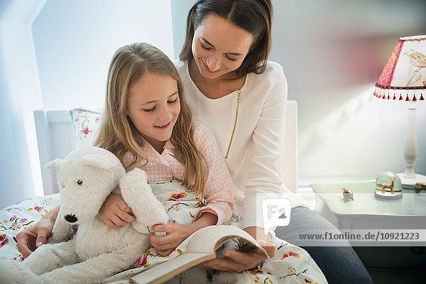 Mutter liest Gutenachtgeschichte mit Tochter im Bett