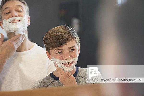 Vater beobachtet den Sohn  der vorgibt  sein Gesicht im Badezimmerspiegel zu rasieren.