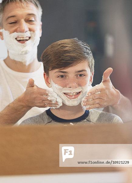 Vater hilft dem Sohn  der vorgibt  sich im Badezimmerspiegel zu rasieren.