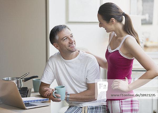 Paar im Schlafanzug beim Reden und Kaffeetrinken am Laptop