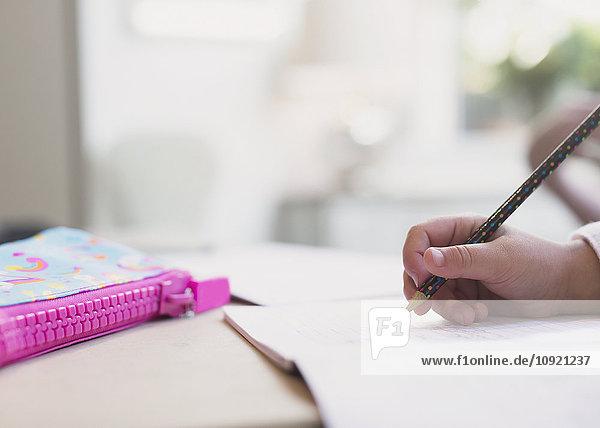 Nahaufnahme Mädchen macht Hausaufgaben mit Bleistift