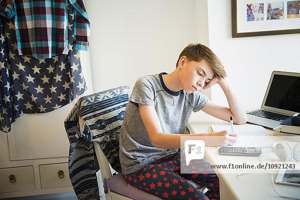 Gelangweilter Junge macht Mathe-Hausaufgaben am Schreibtisch im Schlafzimmer