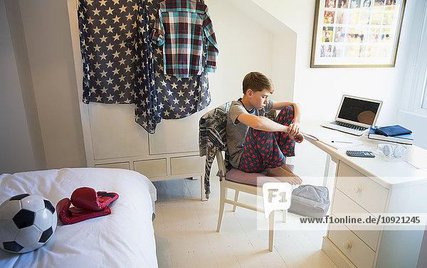 Gelangweilter Junge macht Hausaufgaben am Schreibtisch im Schlafzimmer