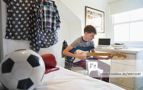 Junge spielt E-Gitarre im Schlafzimmer