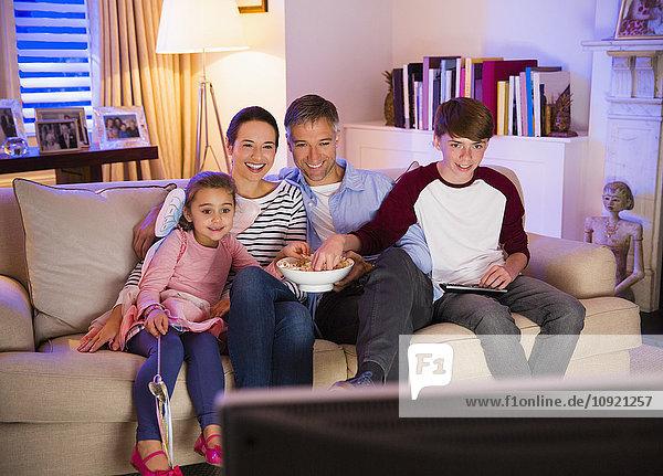 Familie beim Popcornessen und Fernsehen im Wohnzimmer