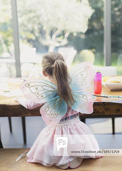 Mädchen in feenhaften Flügeln am Esstisch