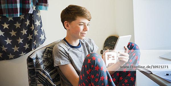 Junge im Schlafanzug mit digitalem Tablett im Schlafzimmer
