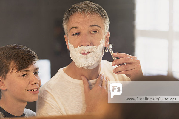 Sohn beobachtet Vater beim Rasieren des Gesichts im Badezimmerspiegel