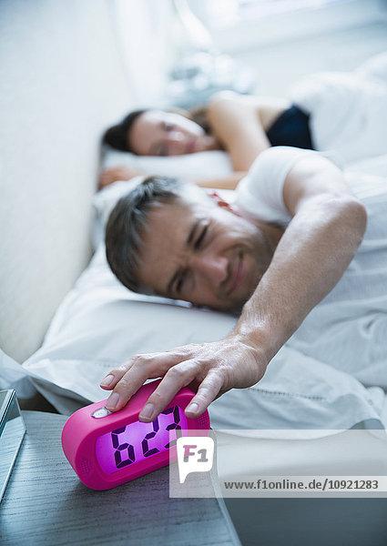 Mann im Bett schaltet morgendlichen Wecker aus