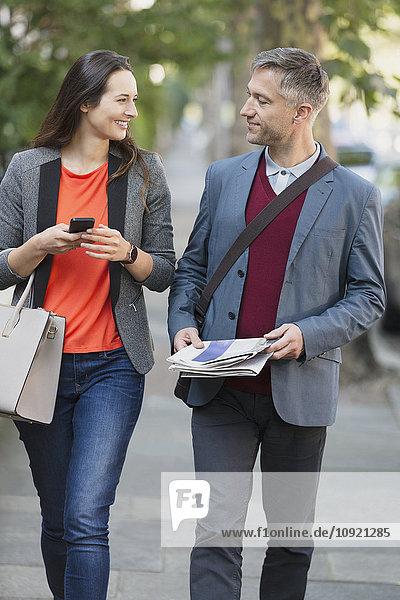 Geschäftsleute beim Gehen und Reden auf dem Bürgersteig