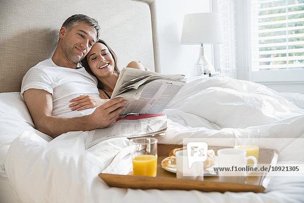 Lächelndes Paar liest Zeitung und genießt Frühstück im Bett