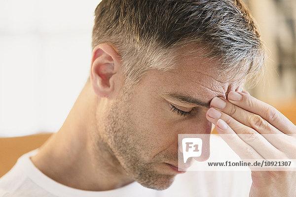 Nahaufnahme eines Mannes mit Kopfschmerzen an der Stirn