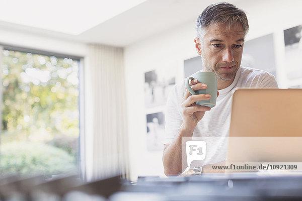Mann trinkt Kaffee und arbeitet am Laptop in der Küche