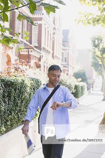 Geschäftsmann mit Zeitung auf dem Bürgersteig und Kontrolle der Armbanduhr
