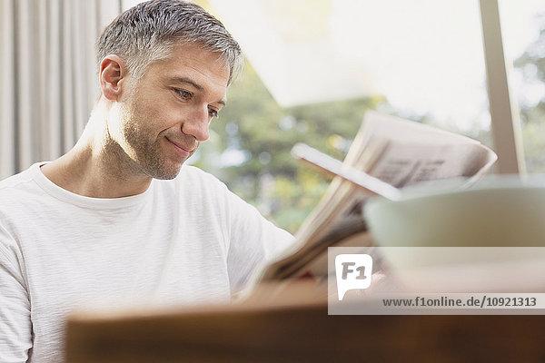 Mann liest Zeitung beim Frühstück