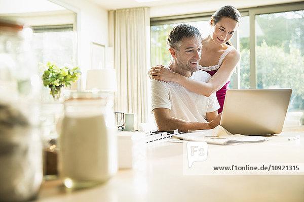 Paar mit Laptop in der Morgenküche