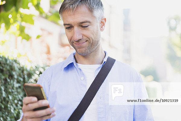Geschäftsmann texting mit Handy im Freien