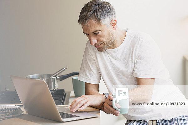 Mann im Pyjama  der Kaffee trinkt und am Laptop in der Küche arbeitet.