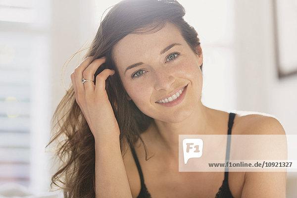 Portrait lächelnde Frau mit Hand im Haar