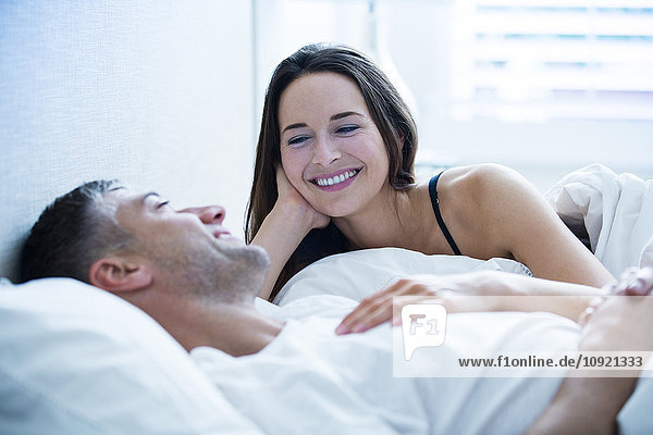 Lächelndes Paar im Bett liegend und redend