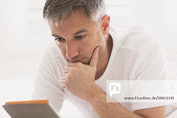 Seriöser Mann mit digitalem Tablett mit Hand am Kinn