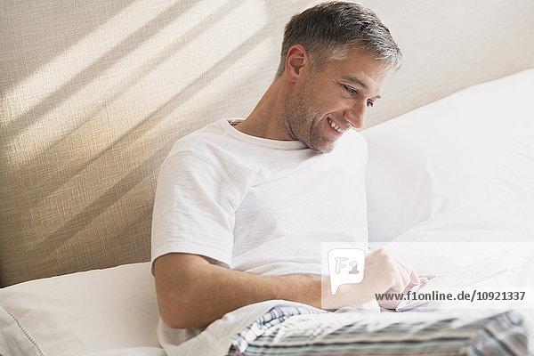 Lächelnder Mann mit digitalem Tablett im Bett