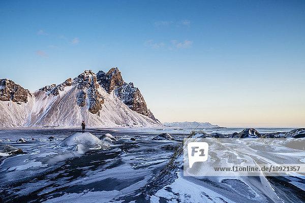 Frau steht in abgelegener  eisiger Landschaft  Hofn  Island