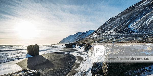 Sonne über eisigem Strand und Bergen  Island