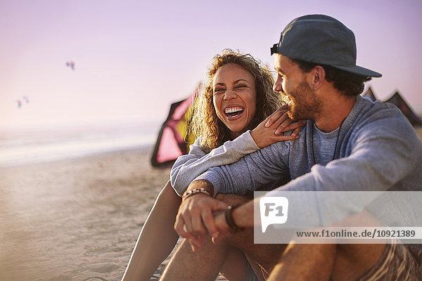 Lachendes Paar am Strand sitzend