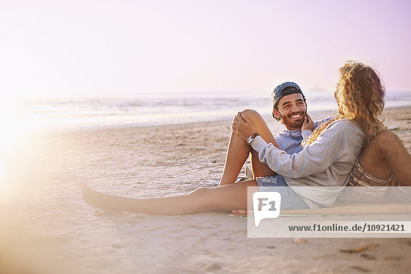 Lächelndes Paar  das sich am Strand bei Sonnenuntergang entspannt und unterhält.
