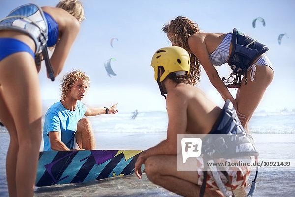 Mann unterrichtet Freunde beim Kitesurfen am sonnigen Strand