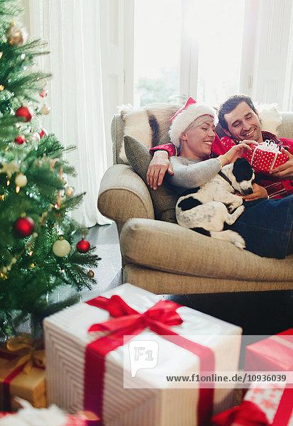 Paar Kuscheln auf Sofa mit Hund am Weihnachtsbaum und Geschenke