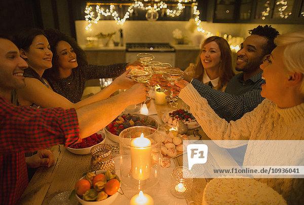 Freunde rösten Sektgläser am Kerzenschein-Tisch