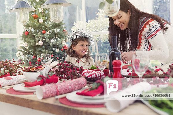 Mutter und Tochter decken den Weihnachtstisch