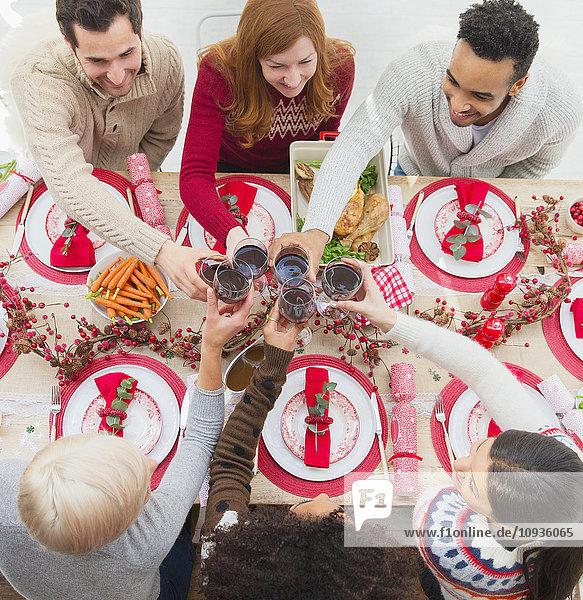 Freunde toasten Weingläser am Weihnachtstisch
