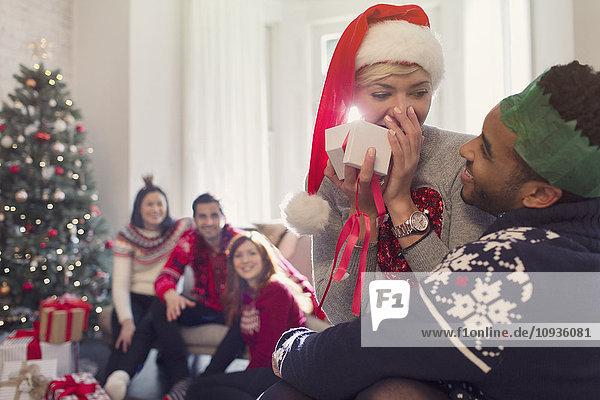 Überraschte Freundin eröffnet Weihnachtsgeschenk vom Freund