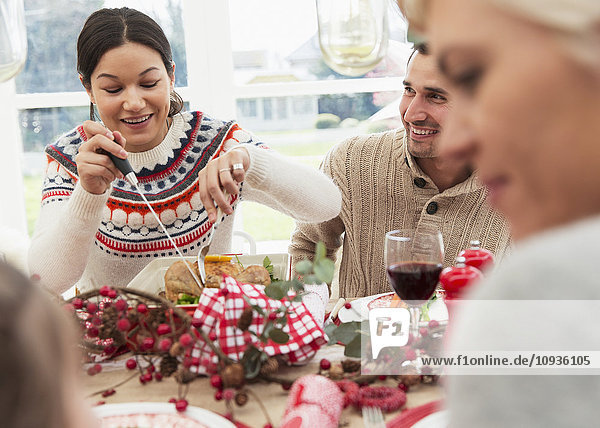 Frau schneidet Weihnachtstruthahn am Tisch