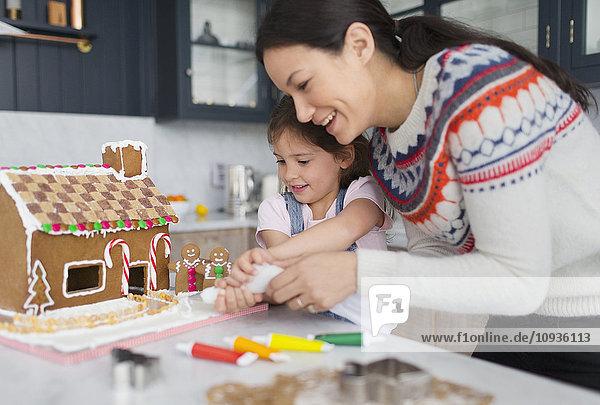 Mutter und Tochter dekorieren Lebkuchenhaus