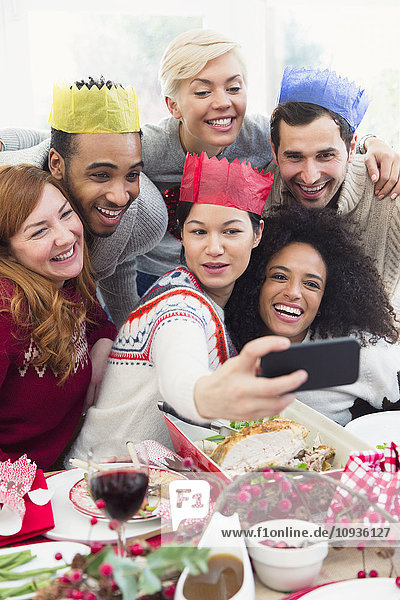 Freunde in Papierkronen  die beim Weihnachtsessen Selfie nehmen