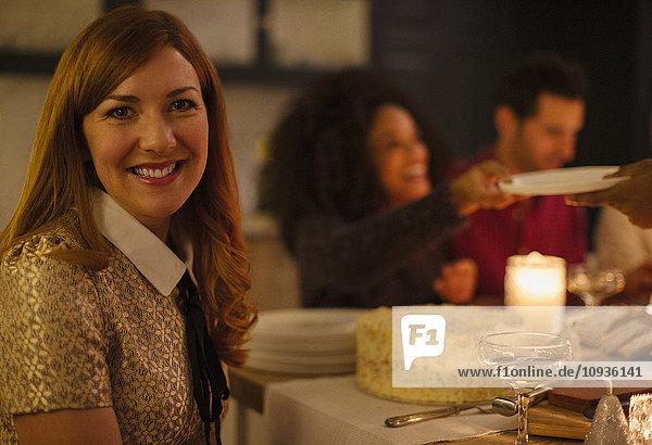Portrait lächelnde Frau am Kerzenleuchttisch