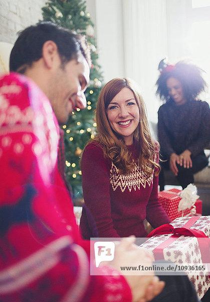 Portrait lächelnde Frau eröffnet Weihnachtsgeschenke mit Freunden