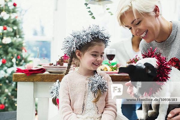 Mutter und Tochter füttern Hund beim Weihnachtsessen