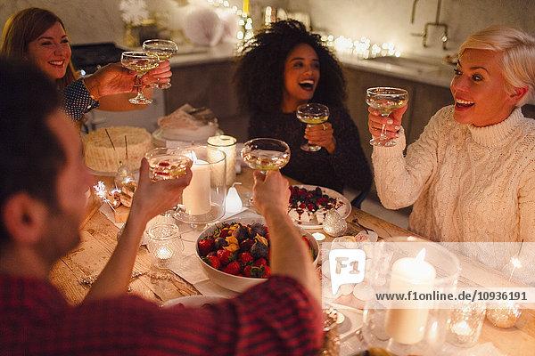 Begeisterte Freunde stoßen beim Weihnachtsessen bei Kerzenschein auf Champagnergläser an.