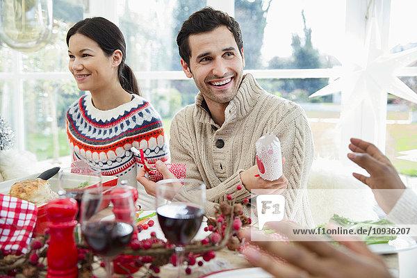 Lächelnder Mann mit Weihnachtsknacker am Esstisch