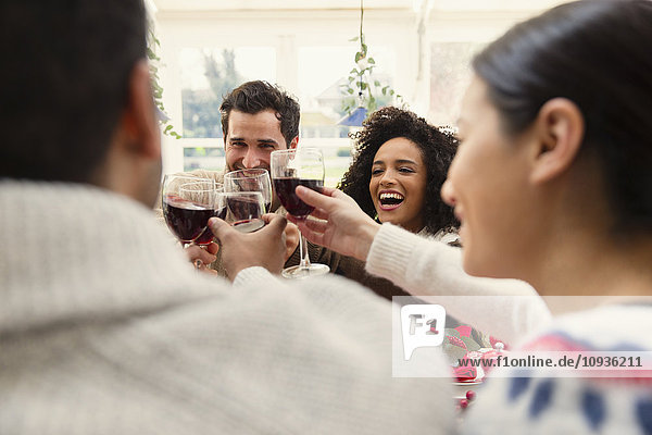 Enthusiastische Freunde stoßen beim Weihnachtsessen auf Weingläser an.